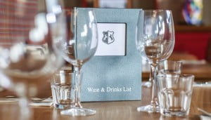 Wine glasses and drinks menu on table